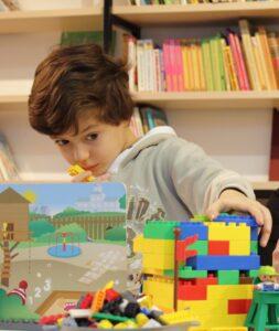 bambino gioca costruzioni lego